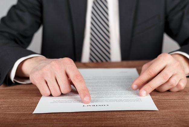Бизнесмен, читая условия делового контракта