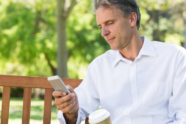 Businessman reading text message on mobile phone