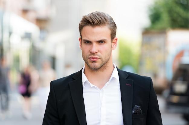 問題を解決する準備ができているビジネスマン。男は手入れの行き届いたエレガントなフォーマルなスーツは、都会の背景を歩きます。昼食時にビジネスマンの深刻なクイックウォーク。ビジネスマンハンサムな魅力的なサラリーマン。
