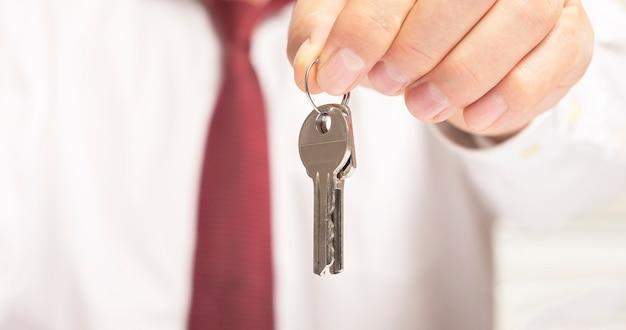 Бизнесмен-риэлтор предлагает ключи от камеры, сидя за офисным столом в рубашке и красном галстуке