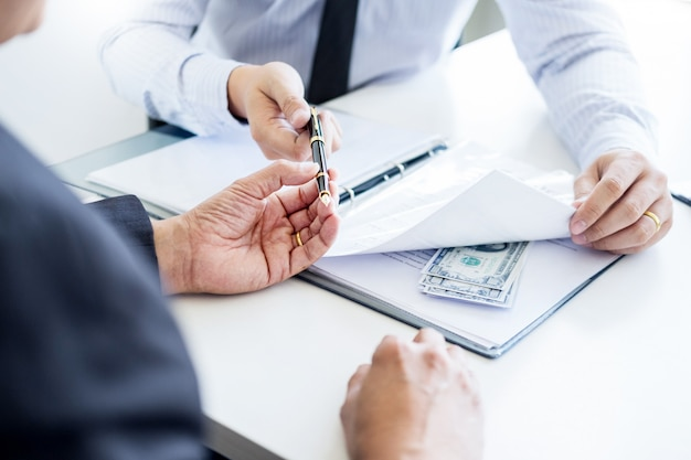 Businessman receive money in file taking bribe and signing a contract corruption concepts.