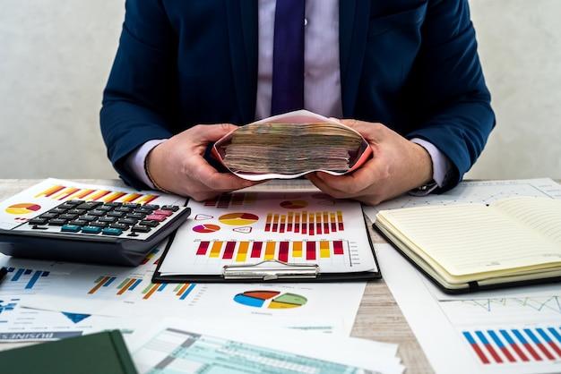 ビジネスマンは会社から封筒に隠された収入を受け取ります。男性はビジネススケジュールで働き、オフィスで利益を維持します。賃金または汚職の概念。