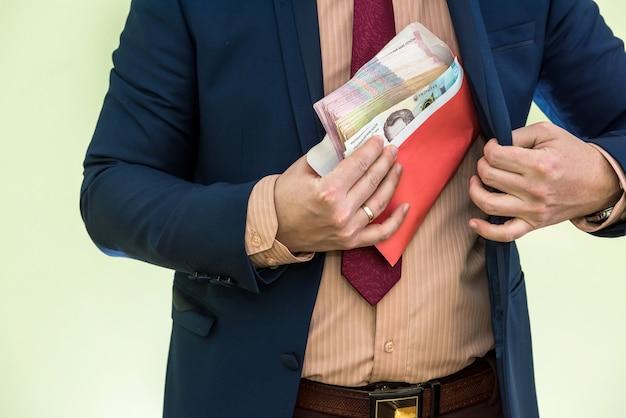 ビジネスマンは封筒の賄賂としてお金を受け取ります。男は封筒にグリブナウクライナのお金の全体の束を与えます