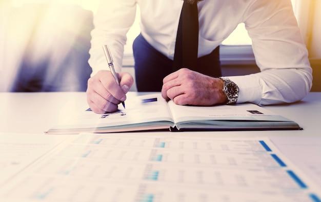 회의 또는 이벤트를 예약하기 위해 데이터를 기록하는 사업가