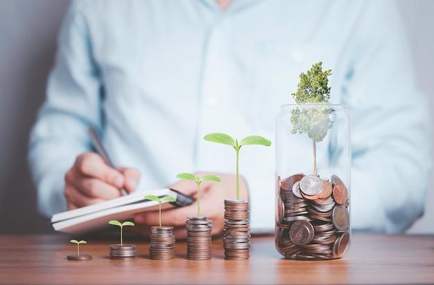 Бизнесмен, записывающий доходы с монетами, укладывающими с ростом растений и банку, экономию денег и концепцию инвестиций в прибыль.