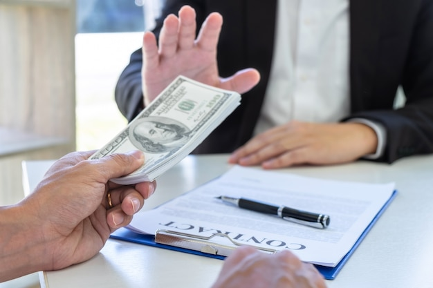 Businessman refusing receive bribe money of their partner to give success the deal contract Premium Photo