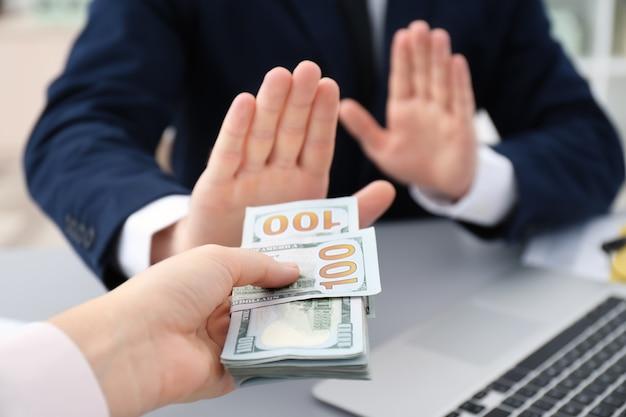 Businessman refusing to take bribe indoors