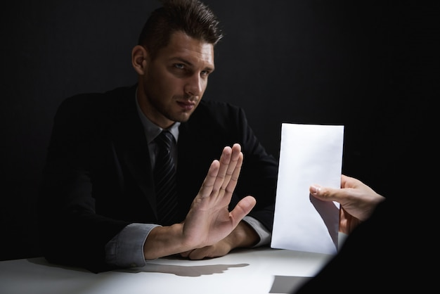 Businessman rejecting bribe money in white envelope offered by his partner