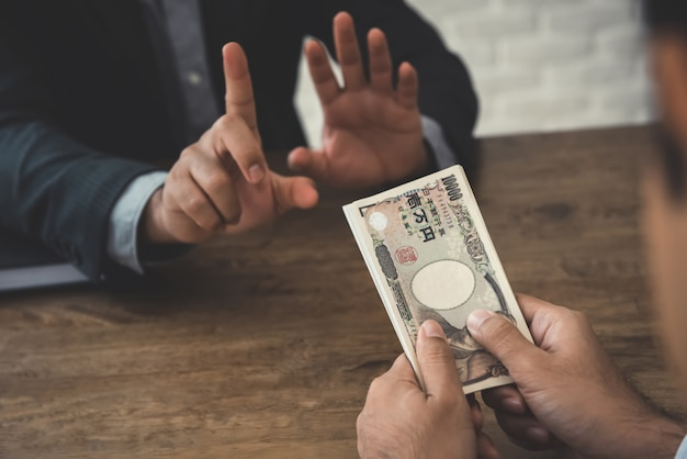 Businessman rejecting money, japanese yen banknotes - anti bribery and corruption concepts