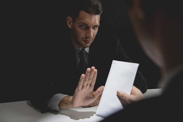 Businessman rejecting money in white envelope offered by his partner