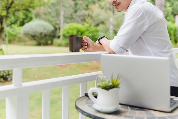 Businessman relax standing on terrace hand holding coffee with laptop on table.