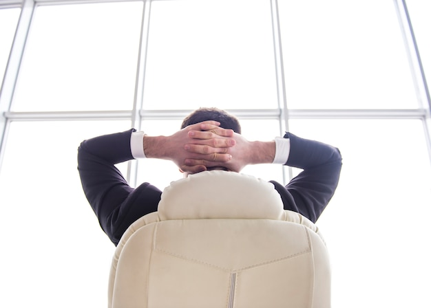 Businessman relaxing in chair of his office with his hands.