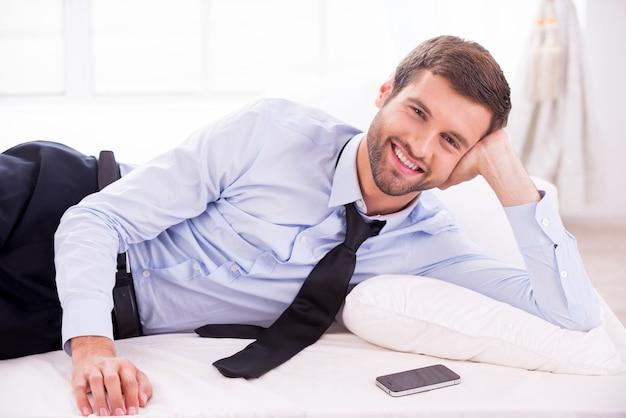 사업가 휴식입니다. 셔츠와 넥타이 침대에 누워 웃 고 잘생긴 젊은 남자