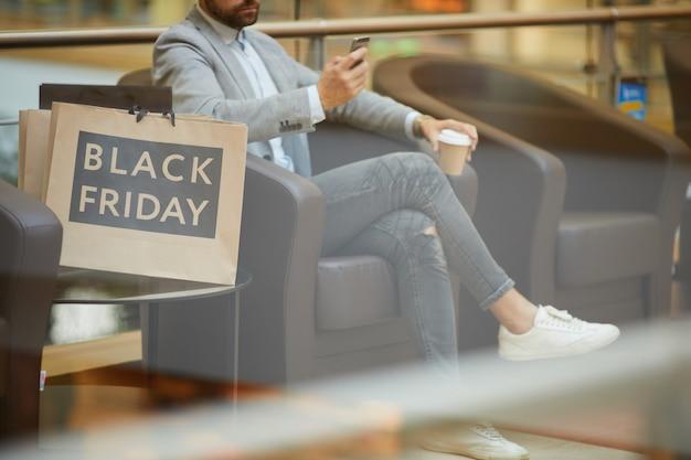 Бизнесмен расслабляющий в торговом центре