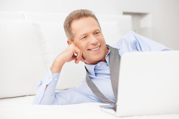 Бизнесмен расслабляющий. улыбающийся седой мужчина в рубашке и галстуке, используя ноутбук, лежа на кровати