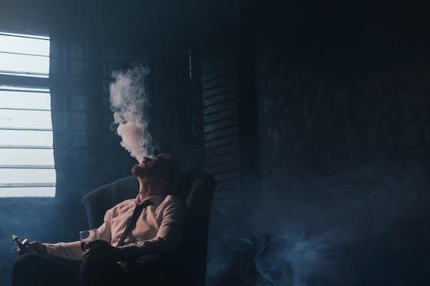 Бизнесмен расслабляющий с vape и алкоголем. темная комната с белым атмосферным дымовым фоном, развлечения для богатых, частный клуб для роскошной жизни со свободным пространством