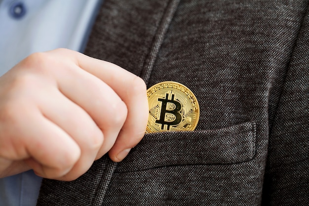 Businessman removing or placing a golden bitcoin in a pocket