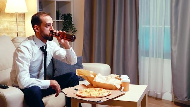 Бизнесмен, отдыхая на диване, пить пиво и есть пиццу в гостиной. расслабляясь после работы, смотря телевизор.
