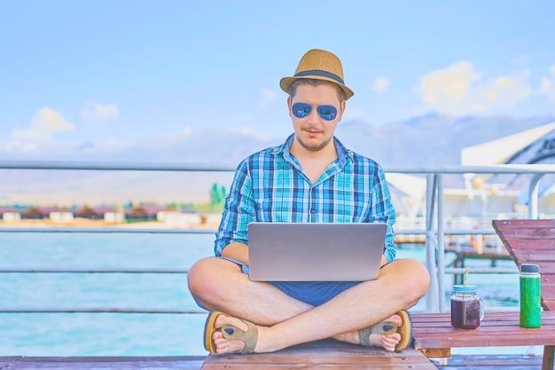 Businessman resting on piers, enjoying summertime in resort spa near sea