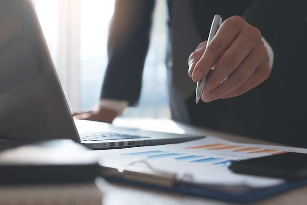ビジネスレポートを確認し、オフィスのテーブルでラップトップに取り組んでいるビジネスマン