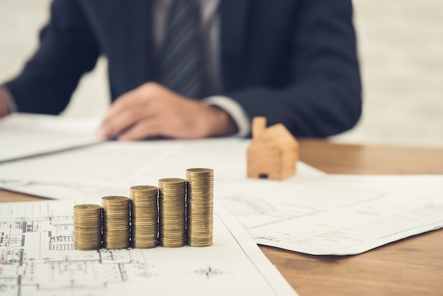 Businessman reviewing document with money and blueprints on the table