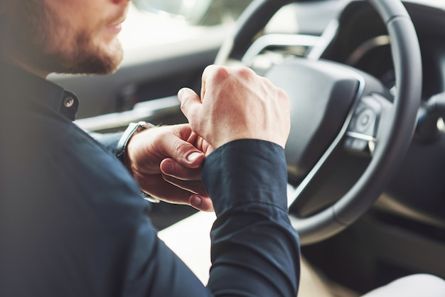 Un uomo d'affari guida la sua macchina, si muove sulla ruota. mano con orologio.