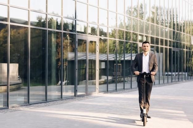 Бизнесмен, езда на электросамокате для деловой встречи в офисе офисных зданий busines