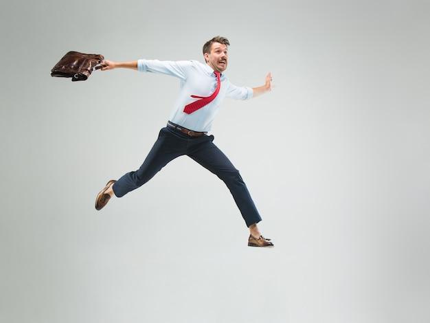 Бизнесмен, бегущий с портфелем, изолированный на серой стене студии