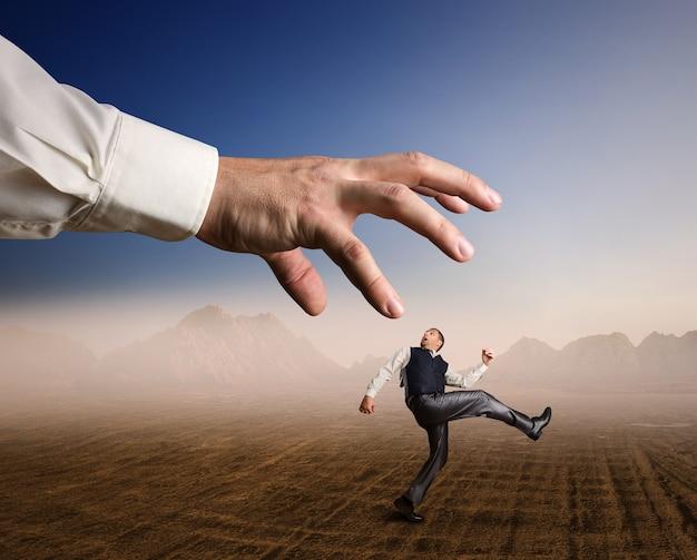 ビジネスマンは大きな腕から砂漠で実行されます