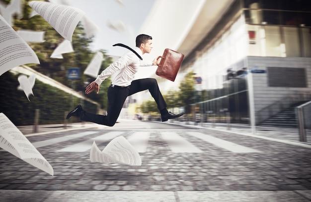 ビジネスマンは彼のバッグを持って仕事に行くために通りを走ります