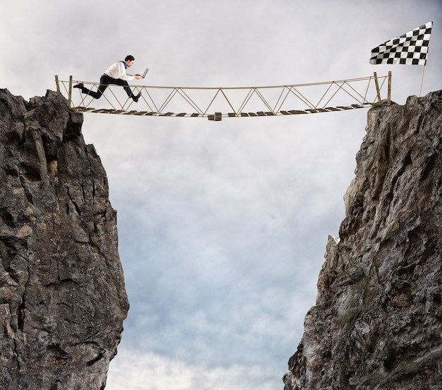 Businessman runs through a shaky bridge to get to the flag. achievement business goal and difficult career concept