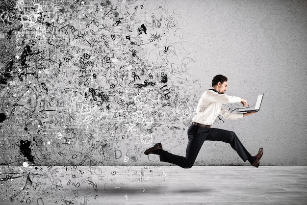 ビジネスマンは彼のラップトップとビジネスプランとプロジェクトのスケッチで実行されます