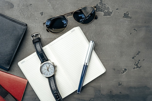 濃い灰色の背景にメモ帳、時計、財布などのビジネスマンのアクセサリーをクローズアップ