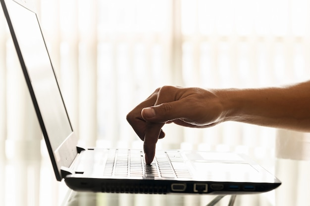 A businessman's finger is pressing down on the laptop's keyboard button in the office.