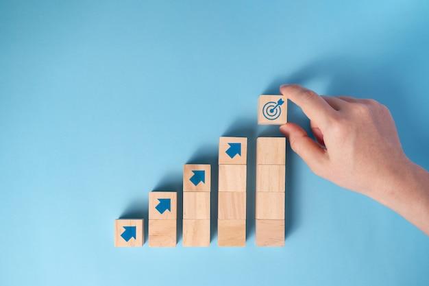 Рука бизнесмена аранжировка деревянных блоков лестница со значком стрелки, концепция бизнес-планирования.