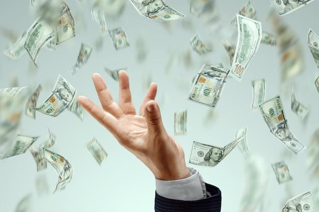 Рука бизнесмена ловит падающие доллары на светлом фоне. понятие вложений, дивидендов, процентов, банковских вкладов.
