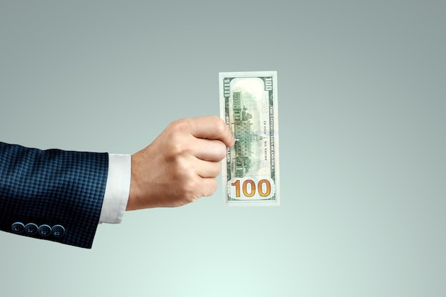 사업가 손을 잡고 100 달러 지폐. 급여, 투자, 기부의 개념.
