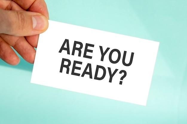 テキストと紙の名刺を持っているビジネスマンの手は準備ができています、クローズアップ水色の背景、ビジネスコンセプト