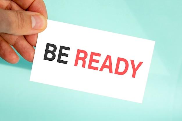 テキストが準備ができて、クローズアップ水色の背景、ビジネスコンセプトと紙の名刺を持っているビジネスマンの手