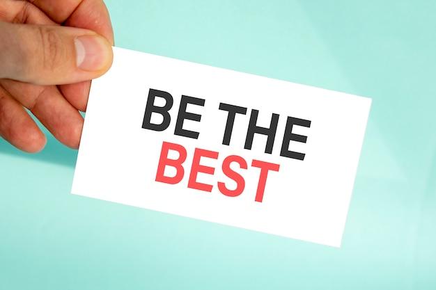 テキストが付いている紙の名刺を持っているビジネスマンの手は最高、クローズアップ水色の背景、ビジネスコンセプト