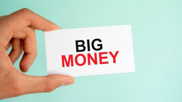 テキストビッグマネー、クローズアップ水色の背景、ビジネスコンセプトと紙の名刺を持っているビジネスマンの手