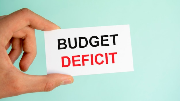 テキスト予算の赤字、クローズアップ水色の背景と紙の名刺を持っているビジネスマンの手