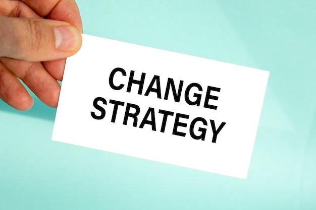 テキスト変更戦略、クローズアップ水色の背景、ビジネスコンセプトと紙の名刺を持っているビジネスマンの手
