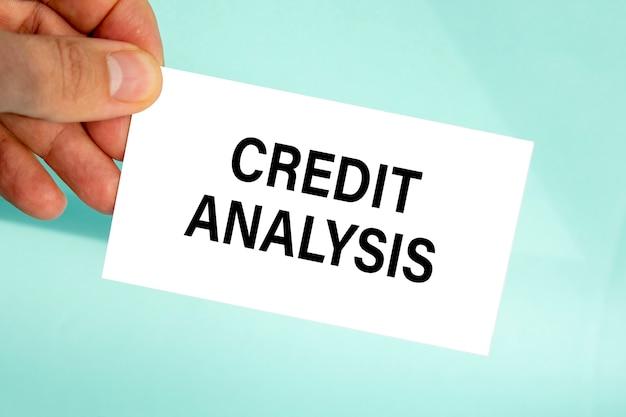 テキストクレジット分析、クローズアップ水色の背景、ビジネスコンセプトと紙の名刺を持っているビジネスマンの手
