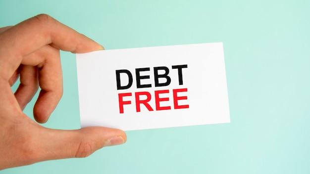 テキスト債務無料、クローズアップ水色の背景、ビジネスコンセプトと紙の名刺を持っているビジネスマンの手
