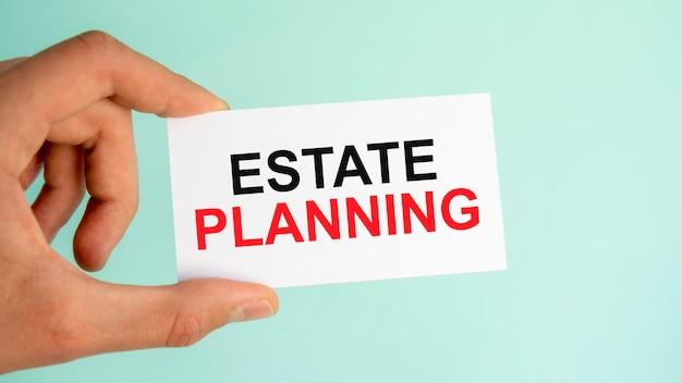 テキストestateplanning、クローズアップ水色の背景、ビジネスコンセプトと紙の名刺を持っているビジネスマンの手