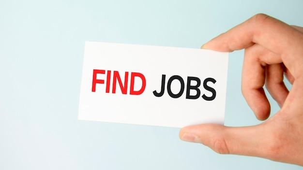 Рука бизнесмена держа бумажную визитную карточку с текстом найти работу, голубой фон крупным планом, бизнес-концепция
