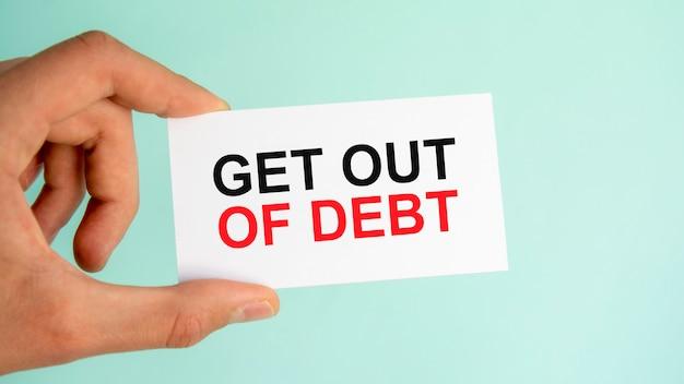 テキストが付いている紙の名刺を持っているビジネスマンの手は借金から抜け出す、クローズアップ水色の背景