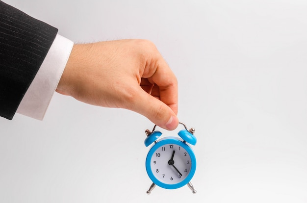 A businessman's hand holds a blue alarm clock on a white background.