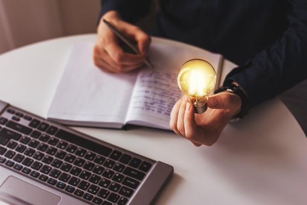 Рука бизнесмена держит зажженную лампочку, идею, инновации и концепцию вдохновения